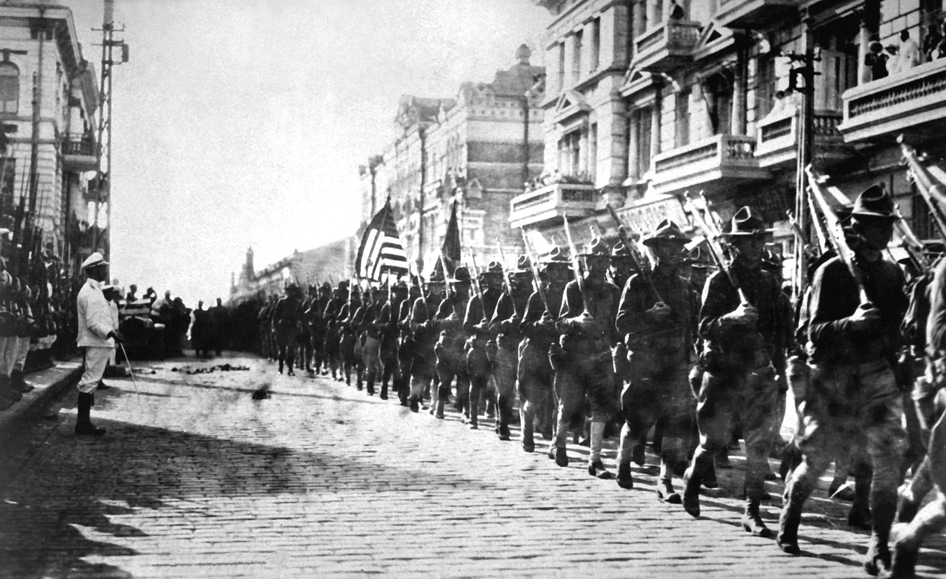 Tropas estadunidenses marcham em Vladivostok, na Sibéria, em agosto de 1918, diante de prédio ocupado por tchecoslovacos. À esquerda da foto, em posição de sentido, fuzileiros navais japoneses observam a marcha.